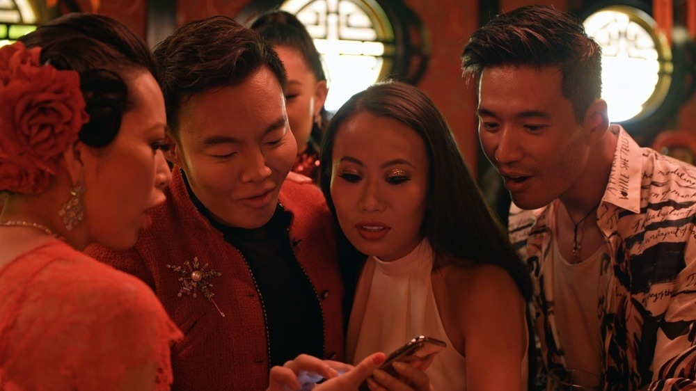 Members of the 'Bling Empire' cast staring a phone