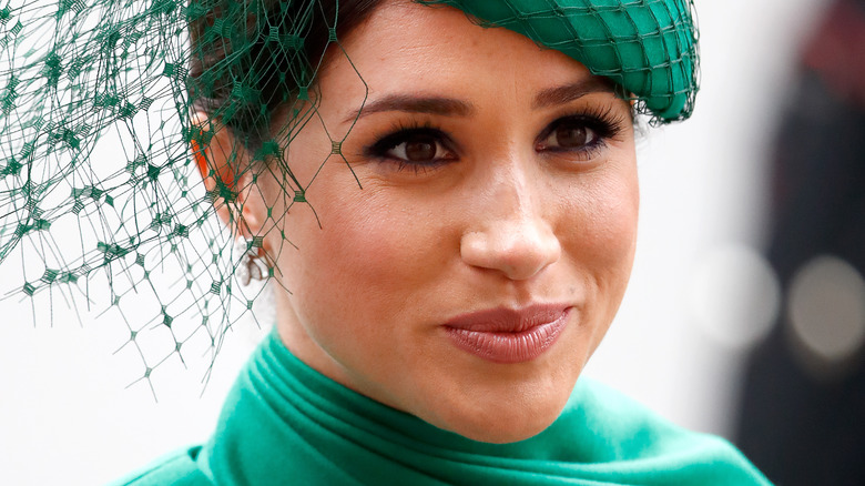 Meghan Markle, the Duchess of Sussex, wearing fascinator with slight smile