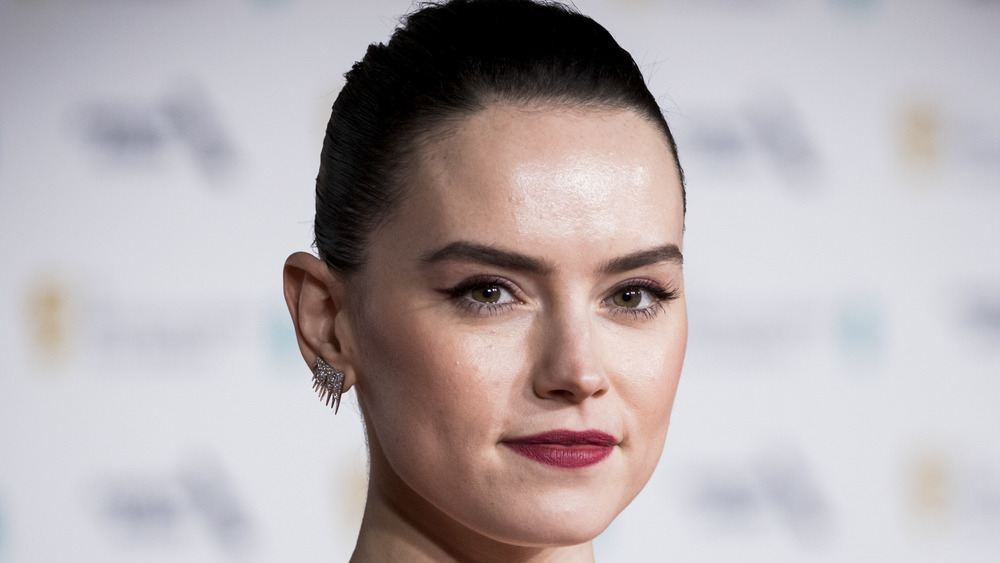 Daisy Ridley wearing red lipstick, spiky earrings and her hair pulled back
