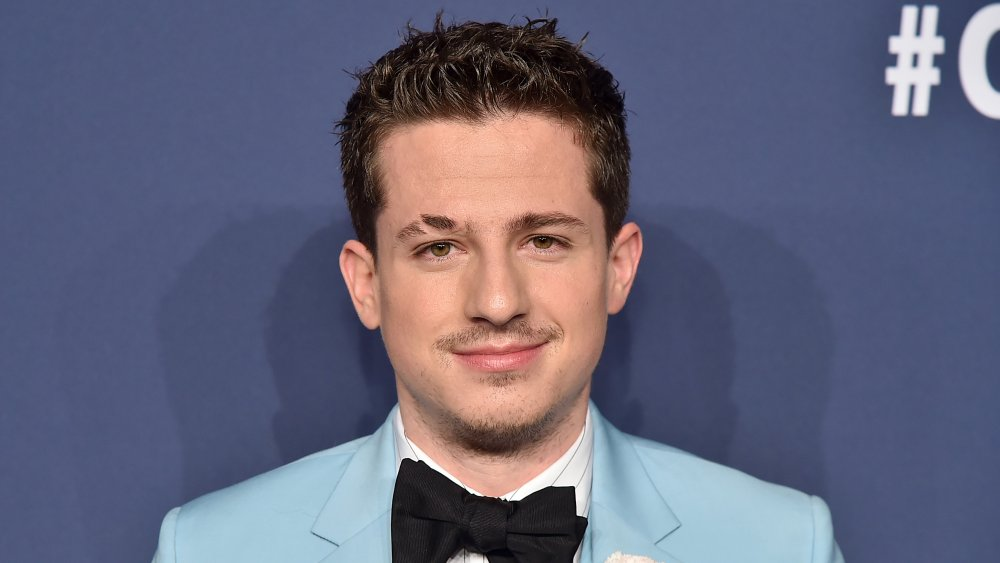 Charlie Puth in a light blue suit with white shirt and black bow tie, grinning while posing on a red carpet