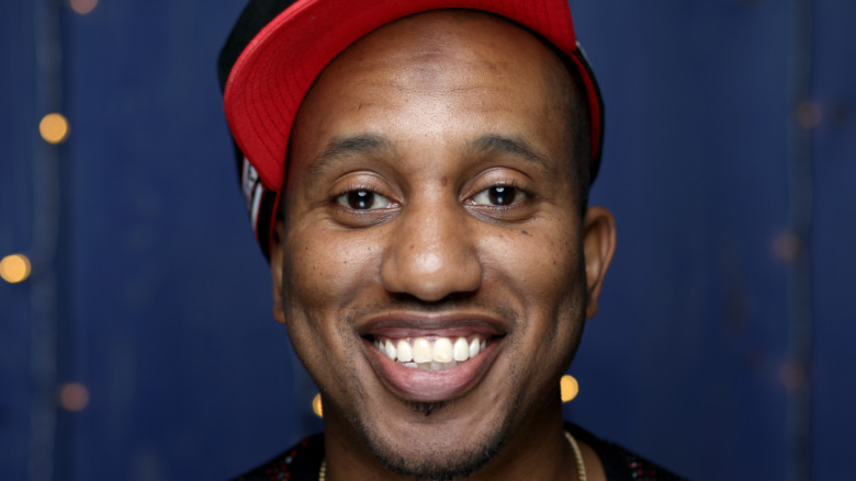 Chris Redd smiling and wearing red hat