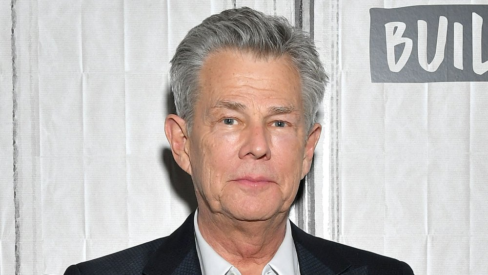 David Foster a black blazer, white shirt combo, with a neutral expression at an event
