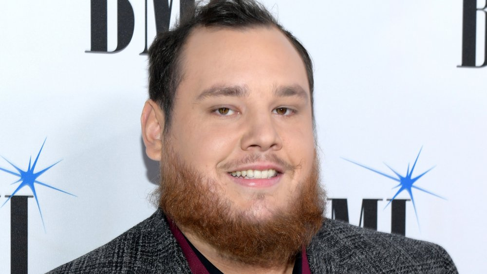 Luke Combs in a grey tweed blazer, smiling at a red carpet event