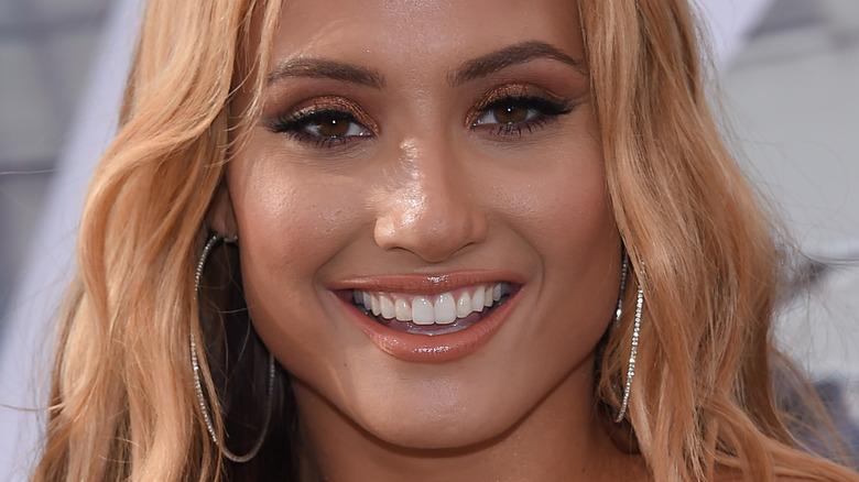 Montana Tucker smiling with hair down and hoop earrings