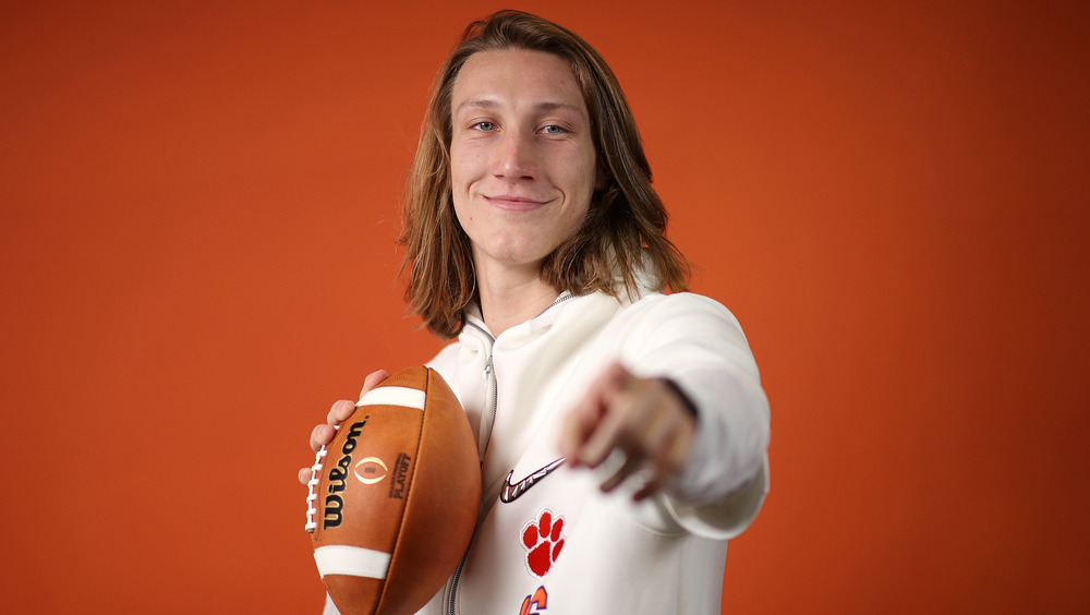 Trevor Lawrence holding a football and pointing at the camera