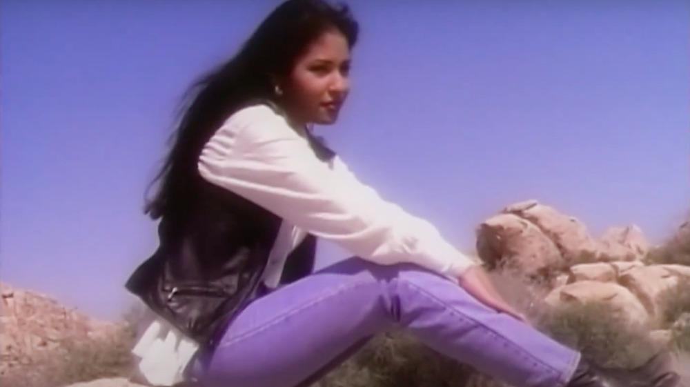 Selena Quintanilla seated on a rock