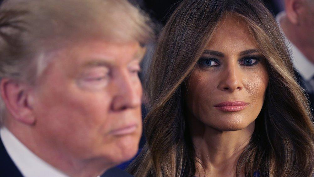 Melania Trump looking at Donald Trump, both with neutral expressions