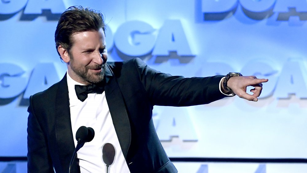 Bradley Cooper pointing off stage during an award show appearance