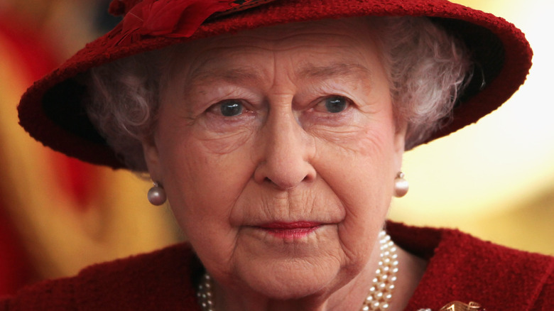 Queen Elizabeth II with serious expression and red hat