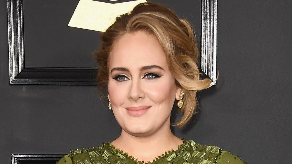 Adele smirking while posing at the Grammys