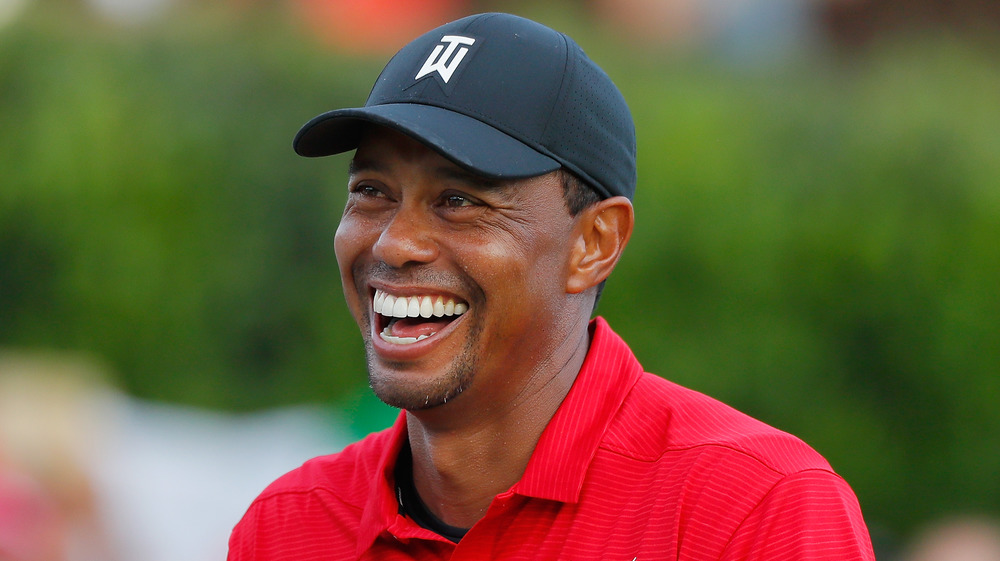 Tiger Woods in baseball cap smiling