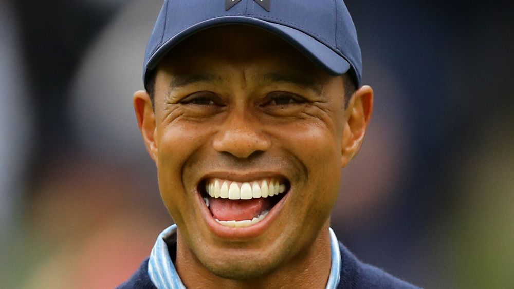 Tiger Woods laughing while playing golf