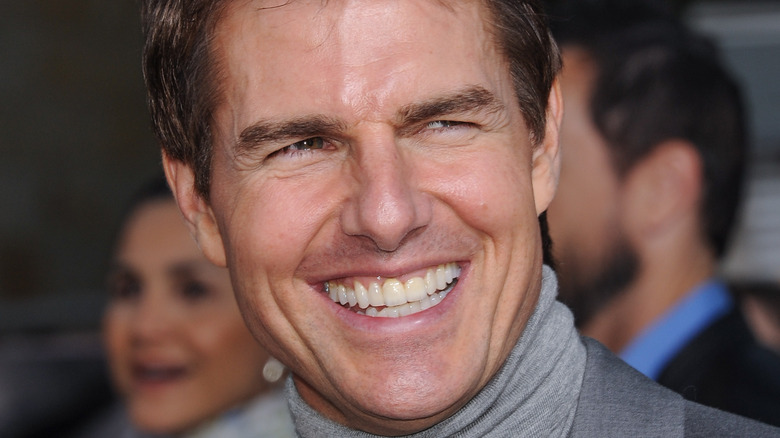 Tom Cruise smiling on a red carpet