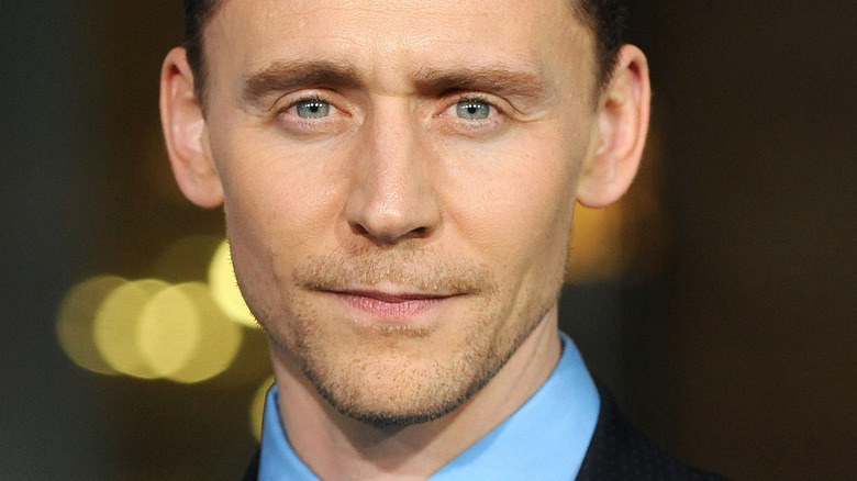 Tom Hiddleston with slight smirk on red carpet