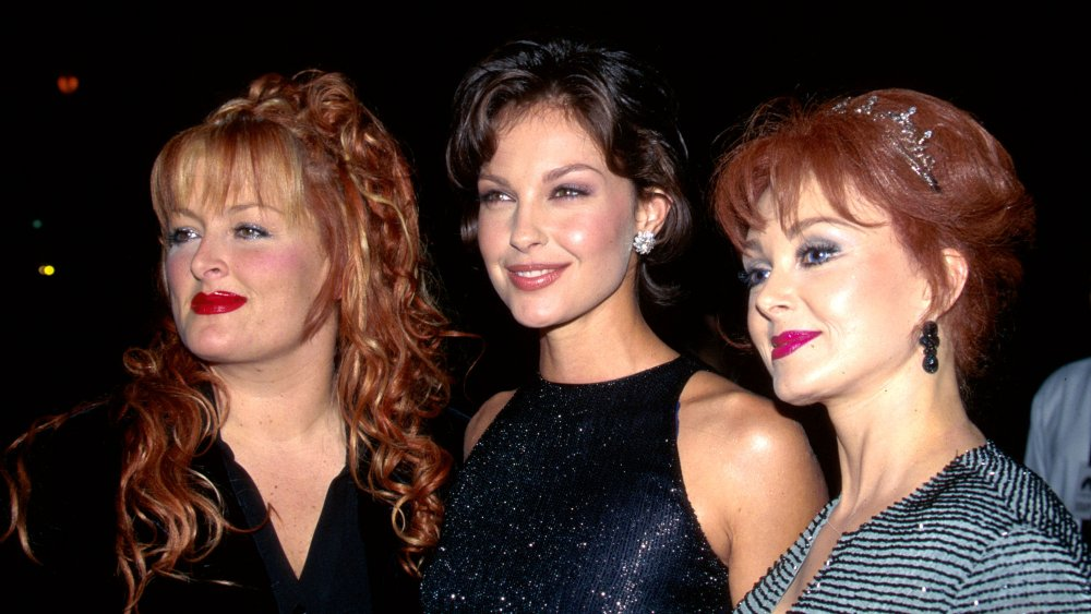 Wynonna Judd, Ashley Judd, Naomi Judd standing together with small smiles at a movie premiere