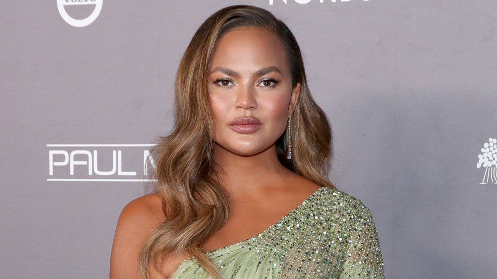 Chrissy Teigen posing in a bejeweled dress with a neutral expression