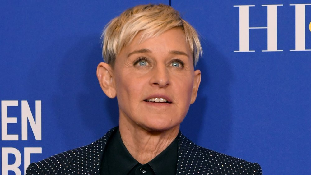 Ellen DeGeneres in a blue polka-dot suit and black shirt, posing with a neutral expression at the 2020 Golden Globes