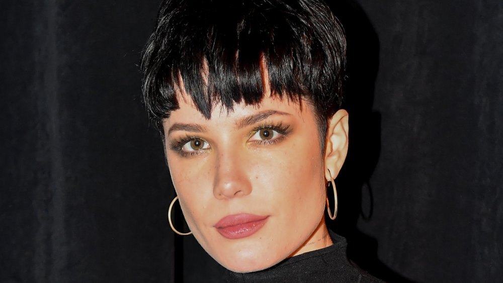 Halsey with short black hair and earrings