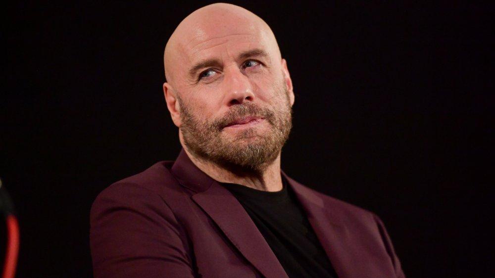 John Travolta in a purple suit, bald
