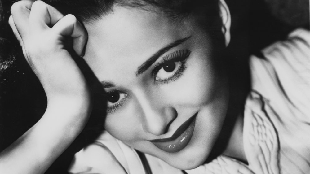 Olivia de Havilland looking straight at the camera with a smile, leaning her head against her hand