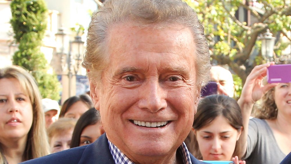 Regis Philbin in a blue blazer and checkered shirt, smiling
