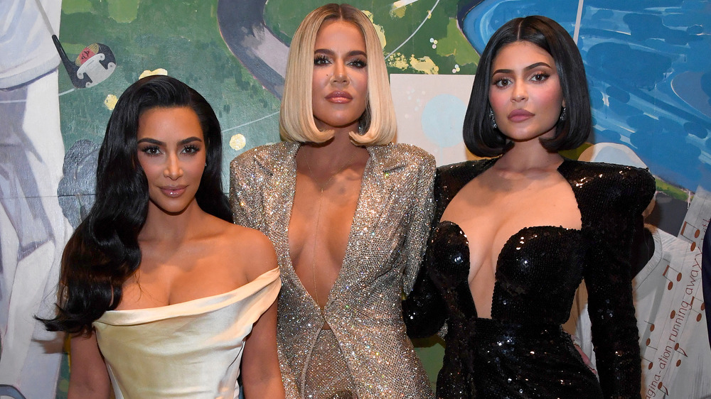 Kim Kardashian, Khloe Kardashian, and Kylie Jenner posing arm in arm together