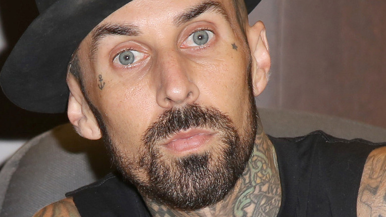 Travis Barker poses for camera in a hat