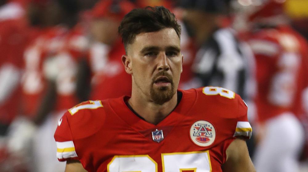 Travis Kelce, serious face, in uniform, on the field, longer hair, goatee