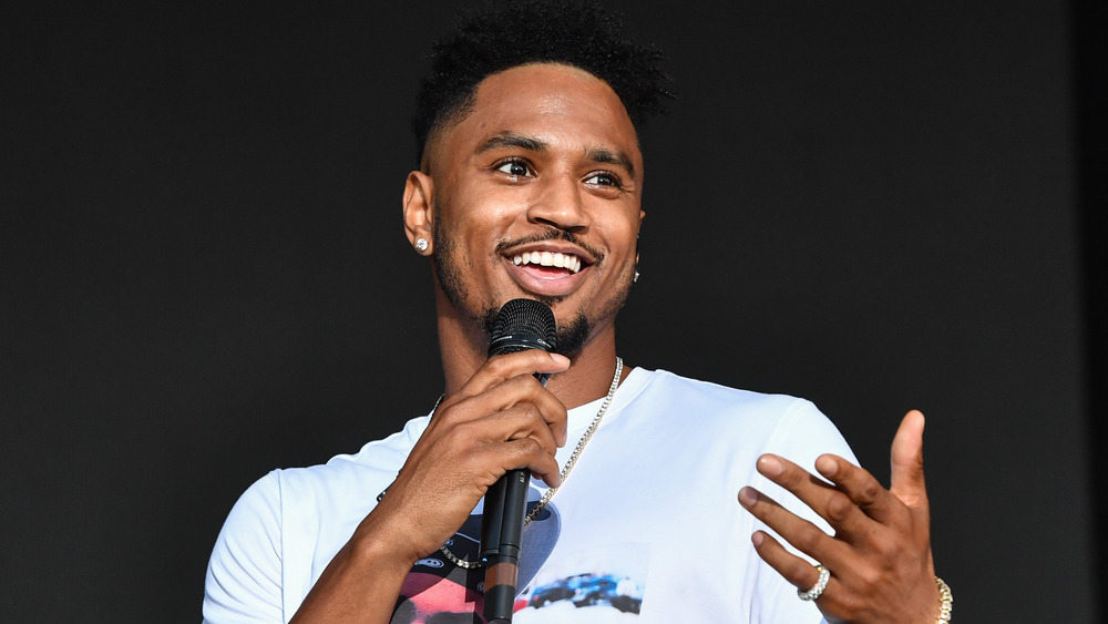 Trey Songz speaking with a microphone on stage