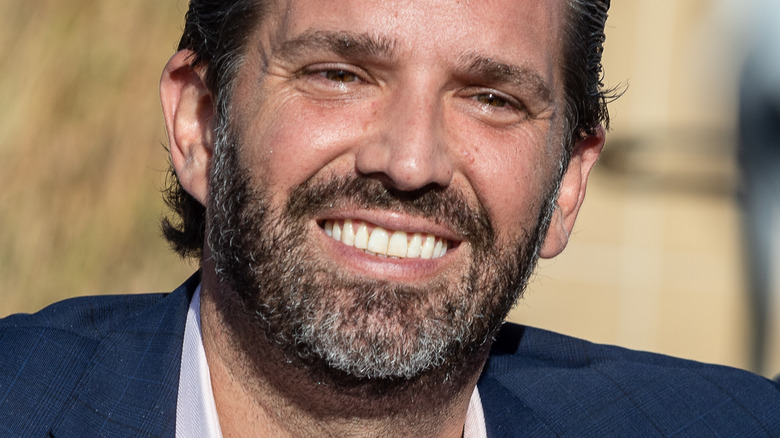 Donald Trump Jr smiling and looking down to the side