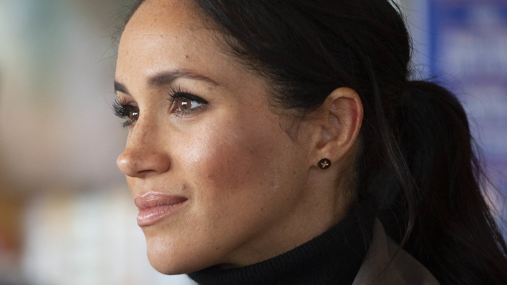 Meghan Markle looking off into the distance wearing a ponytail