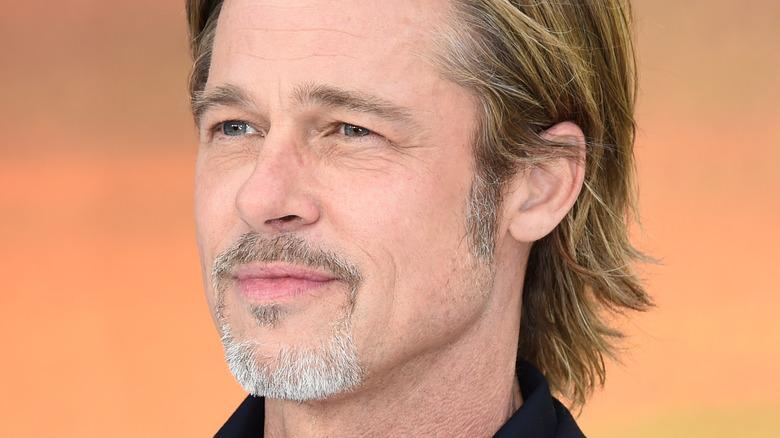 Brad Pitt smirking in front of an orange wall