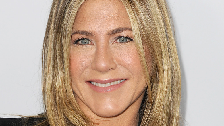 Jennifer Aniston smiles in a black outfit