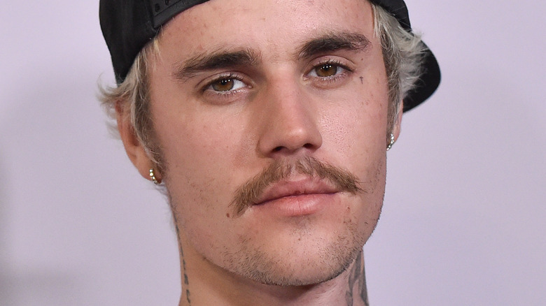 Justin Bieber wearing cap and looking at the camera with serious expression