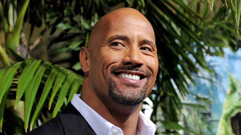 Dwayne 'The Rock' Johnson smiling in front of palm tree