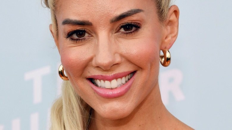 Heather Rae Young with wide smile and gold hoop earrings