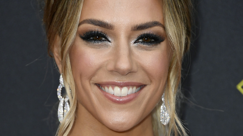 Jana Kramer, smiling, wearing makeup, big earrings, hair up, 2019 photo