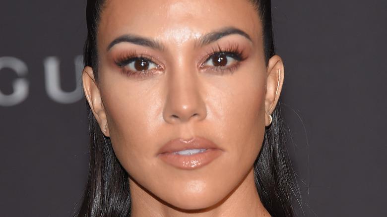 Kourtney Kardashian, hair pulled back into pony tail, 2018 photo, wearing makeup, wearing black