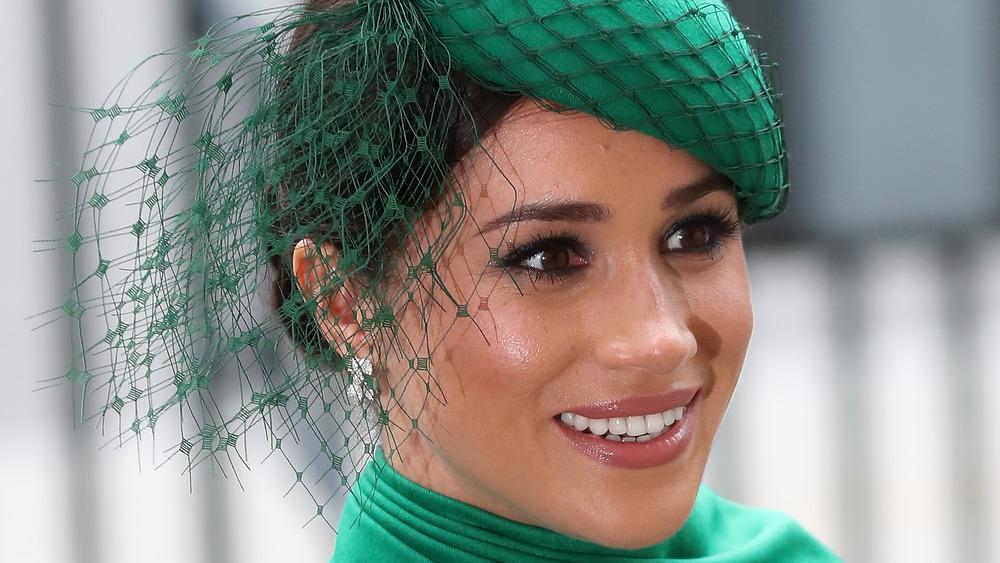 Meghan Markle smiling in green hat