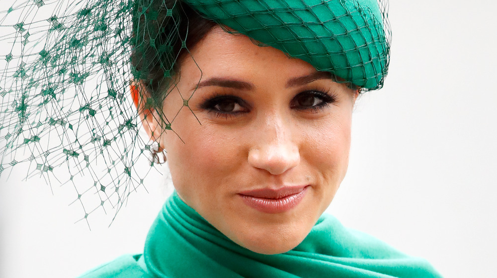 Meghan Markle, the Duchess of Sussex, smiling and wearing emerald green
