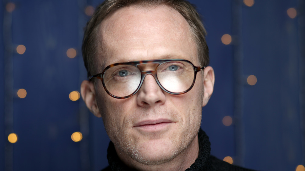 Paul Bettany looks into the camera wearing rimmed glasses