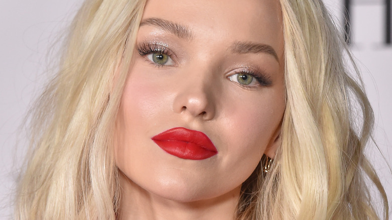 Dove Cameron wearing red lipstick with slight smile