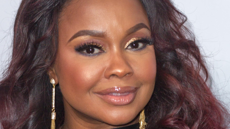 Phaedra Parks, smiling, hair down, wearing makeup and earrings, 2019 photo