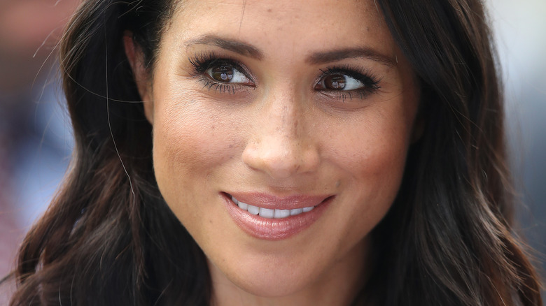 Meghan Markle smiling and looking to the side