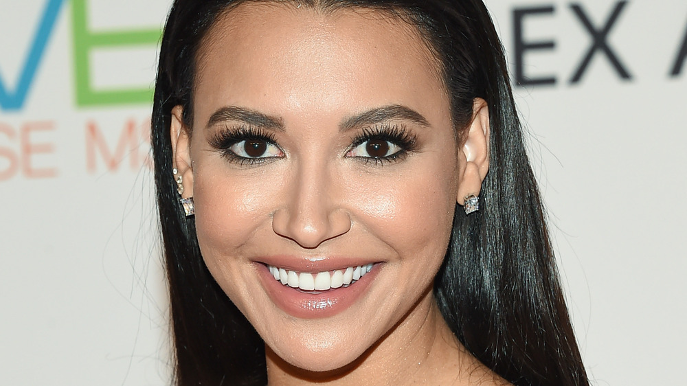 Naya Rivera smilng for cameras wearing diamond earrings