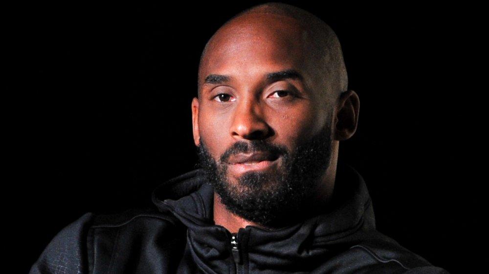 Kobe Bryant in a black jacket looking at camera