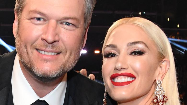 Gwen Stefani and Blake Shelton smiling at an event