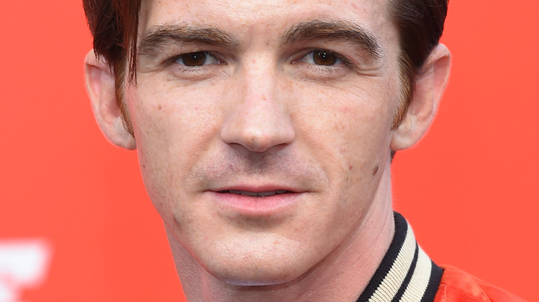 Drake Bell with serious expression in front of orange background