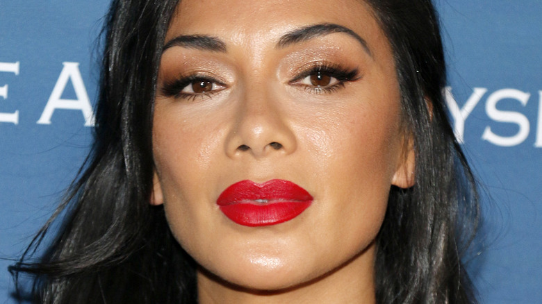 Nicole Scherzinger looking at camera with serious expression and red lipstick
