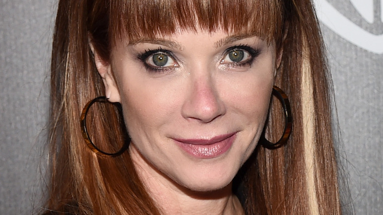 Lauren Holly smiling at camera with bangs
